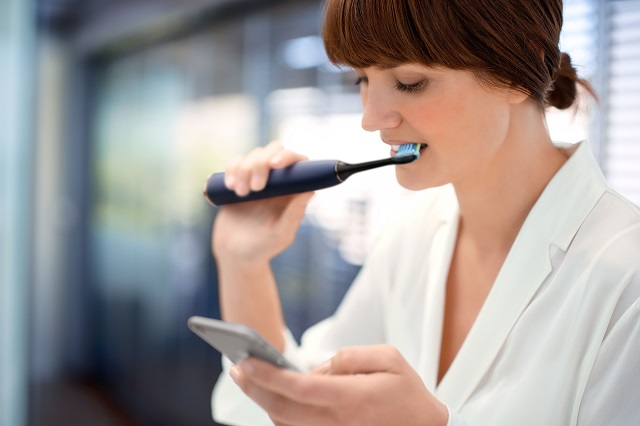 This photo shows someone using a Philips DiamondClean Smart toothbrush and app